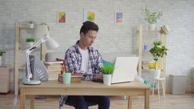 Młodego azjatykciego mężczyzny studencki używa laptop zbiory