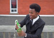 Młodego biznesmen butelki szampańskiego wina alkoholu gratulacje iskrzasty sukces obraz stock