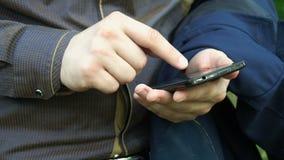 Młodego biznesmena pisać na maszynie wiadomość na telefonie zdjęcie wideo
