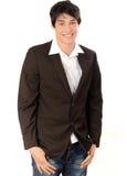 Młodego biznesmena uśmiechnięta pozycja z rękami w kieszeni. Obraz Royalty Free