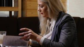 Młodego bizneswomanu czytelnicza gazeta i pić kawa w kawiarni zdjęcie wideo