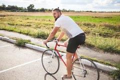 Młodego brodatego modnisia napędowy bicykl Fotografia Stock