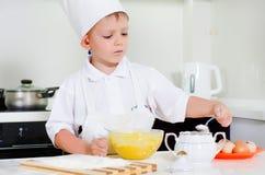 Młodego chłopiec szefa kuchni sumujący składniki jego rzucają kulą Obraz Royalty Free