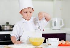 Młodego chłopiec szefa kuchni sumujący składniki jego rzucają kulą Fotografia Royalty Free