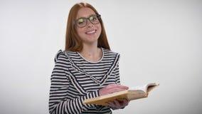 Młodego cukierki spokoju imbirowa dziewczyna z szkłami jest czytelniczym książką, dopatrywanie przy kamerą, ono uśmiecha się, bia zdjęcie wideo