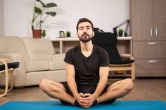 Młodego człowieka ćwiczy joga w jego żywym pokoju fotografia stock