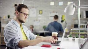 Młodego człowieka śpiewacki obsiadanie przy biurowym biurkiem z laptopem otaczającym różnorodnymi kolegami, gnuśny pracownika mar zbiory