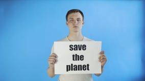 Młodego człowieka aktywista oprócz z planeta plakatem na błękitnym tle zdjęcie wideo