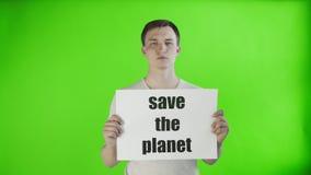 Młodego człowieka aktywista oprócz z planeta plakatem na chroma klucza tle zbiory