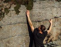 Młodego człowieka arywisty wspinaczka na skale w małym pęknięcie kamieniu zdjęcia stock