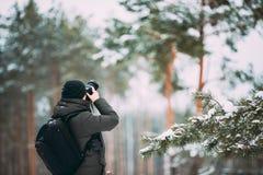 Młodego Człowieka Backpacker Z fotografii kamerą Bierze fotografię W zima Śnieżnym Lasowym Aktywnym hobby Wycieczkowicza odprowad zdjęcie stock
