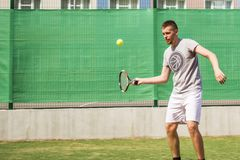 Młodego człowieka beginner gracz w tenisa robi sportom na sądzie na letnim dniu obrazy stock