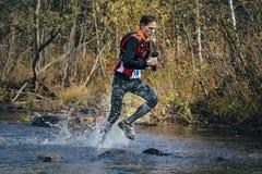 Młodego człowieka biegacza pluśnięcia woda w rzece, podczas krzyżować halną rzekę obrazy stock