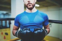 Młodego człowieka bokserski trening na pierścionku w sprawność fizyczna klubie Kaukaski męski bokser w czarnych rękawiczkach Mięś Zdjęcia Royalty Free