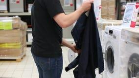 Młodego człowieka brać odziewa z pralki w dużym sklepie Komiczny wideo zdjęcie wideo