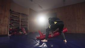 Młodego człowieka ciupnięcia atrapa uderza pięścią torbę w gym podczas ćwiczyć bojową technikę zdjęcie wideo