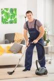 Młodego człowieka cleaning dywan z próżniowym cleaner zdjęcia stock
