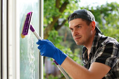 Młodego człowieka cleaning okno z kwaczem Nadokienna płuczka Fachowa cleaning firma fotografia stock