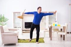 Młodego człowieka cleaning podłoga z miotłą zdjęcia stock