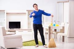 Młodego człowieka cleaning podłoga z miotłą obrazy royalty free