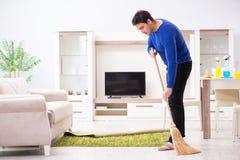 Młodego człowieka cleaning podłoga z miotłą fotografia stock