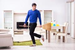 Młodego człowieka cleaning podłoga z miotłą obraz royalty free