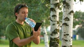 Młodego człowieka cyklisty dotyka pastylka blisko brzozy i napoju wody od butelki Przeciw tłu zieleni pole i zbiory