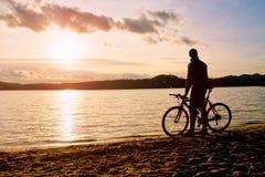 Młodego człowieka cyklisty sylwetka na niebieskim niebie i zmierzchu nad plaża Rowerzysta przy końcówką sezon przy jeziorem Zdjęcia Royalty Free