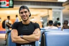 Młodego człowieka czekanie w siedzącym terenie przy lotniskiem lub stacją zdjęcie royalty free