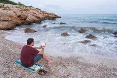 Młodego człowieka czytanie na Śródziemnomorskiej plaży obraz stock