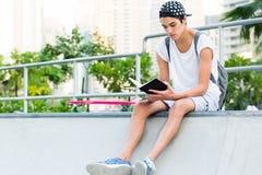 Młodego człowieka czytanie przy deskorolka parkiem obraz stock