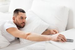 Młodego człowieka dojechanie dla smartphone w łóżku Obrazy Royalty Free