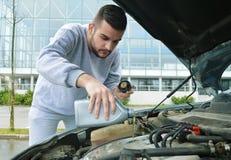 Młodego człowieka dolewania olej w samochód Fotografia Stock