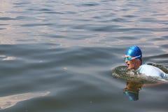 Młodego człowieka dopłynięcie w rzece w błękitnej nakrętce Zdjęcie Stock