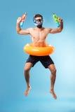 Młodego człowieka doskakiwanie jest ubranym pływackiego okrąg i szkła fotografia stock