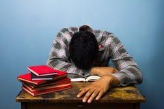 Młodego człowieka dosypianie przy biurkiem po studiować Obraz Royalty Free
