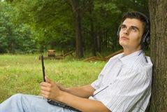 Młodego człowieka działanie na laptopie w parku zdjęcia royalty free