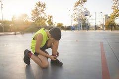 Młodego człowieka gracz koszykówki wiąże shoelaces obrazy stock