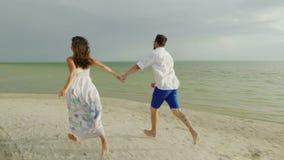Młodego człowieka i kobiety chwyta ręki, bieg bosy wzdłuż plaży Szczęśliwi wakacje i miesiąc miodowy 4K zwolnionego tempa wideo zbiory