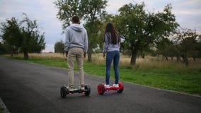 Młodego człowieka i kobiety jazda na Hoverboard w parku zadowolone technologie nowy ruch Zamyka Up Podwójny koło zdjęcie wideo
