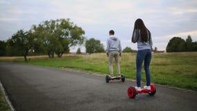 Młodego człowieka i kobiety jazda na Hoverboard w parku zadowolone technologie nowy ruch Zamyka Up Podwójny koło zbiory