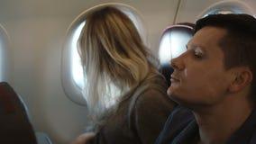 Młodego człowieka i kobiety obsiadanie blisko okno i patrzeć na widoku outside Para podróżuje samolotem wpólnie zbiory wideo