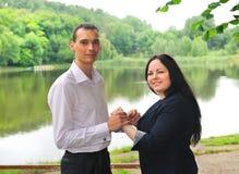 Młodego człowieka i kobiety pozycja na brzeg jezioro. Obraz Stock