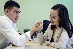 Młodego człowieka i kobiety walka na jego rękach przy biurkiem w biurze dla miejsca Dyryguje, przewodzi, Bitwa płcie, potomstwa d Zdjęcia Royalty Free