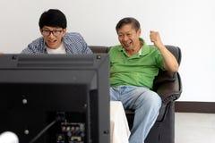 Młodego człowieka i starego człowieka ojca syna zegarka futbol Fotografia Stock