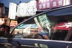 Młodego człowieka jeżdżenie przez Pekin przy nocą, iluminujący sklepów znaki odbijał z okno samochód Zdjęcia Stock
