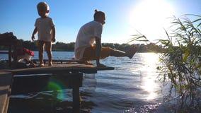 Młodego człowieka joga ćwiczy ćwiczenie na krawędzi drewnianego jetty przy jeziorem na pogodnym letnim dniu Małe dziecko i jego t zbiory wideo
