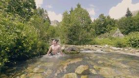 Młodego człowieka kąpanie w wodzie rzecznej i chwiania mokrym włosianym zwolnionym tempie zdjęcie wideo