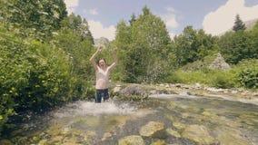 Młodego człowieka kąpanie w zimnej rzece i chełbotania wodnym zwolnionym tempie zbiory