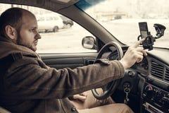 Młodego człowieka kierowca używa smartphone w samochodzie zdjęcie stock